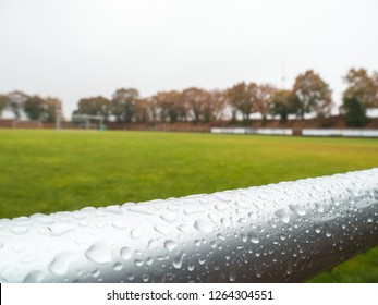 close-up shot of wet hand rails at Rural grass soccer pitch in Germany