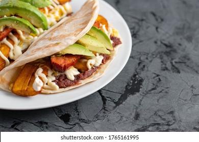 A closeup shot of a white plate with delicious Honduran baleadas on a black textured surface