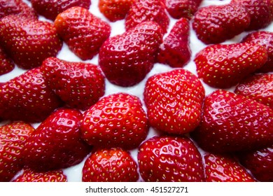 Close-up shot of whole strawberries on a pie from above
