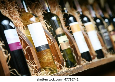 Closeup shot of wine shelf. Bottles lay over straw. Wine cellar.