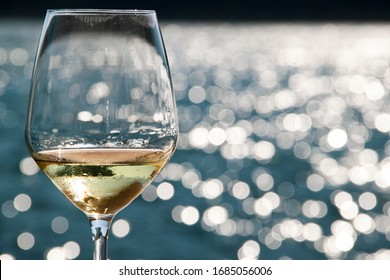 Close-up shot of wineglass with white wine in it and lipstick prints on top of glass, such a lady