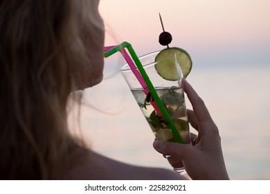 Close-up shot of a woman drinking refreshing mojito cocktail with a straw. Holidays and summer vacation