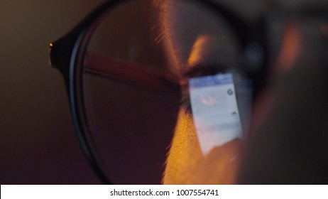 Close-up shot of woman eyes in glasses reflecting a working computer blue screen. Reflection of screen of tablet on woman's eyes with glasses macro view