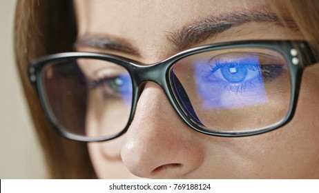 Close-up shot of woman eyes in glasses reflecting a working computer blue screen