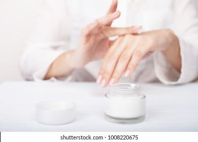 Closeup shot of woman hands applying moisturizing hand cream