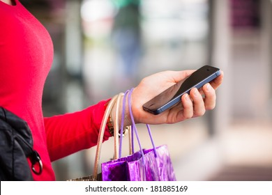 A close-up shot of a woman holding a cell phone or mobile phone whilst out shopping,