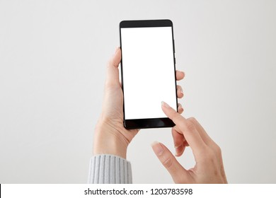 Closeup shot of a woman holding  typing on mobile phone isolated on white background Blank screen to put it on your own webpage or message