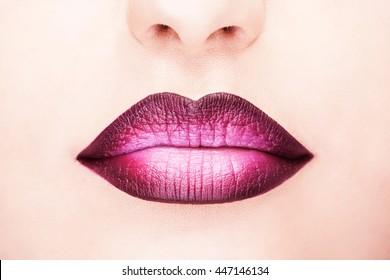 Close-up shot of woman lips with glossy fuchsia lipstick