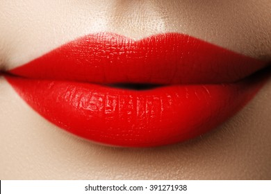 Close-up shot of woman lips with red lipstick. Beautiful perfect lips. Sexy mouth close up. Beautiful wide smile of young fresh woman with full lips