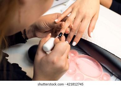 Closeup shot of a woman in nail salon receiving a manicure.