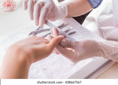 Closeup shot of a woman in a nail salon receiving a manicure by a beautician with nail file.