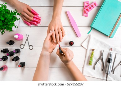 Closeup shot of a woman in a nail salon receiving a manicure by a beautician with nail file. Woman getting nail manicure.