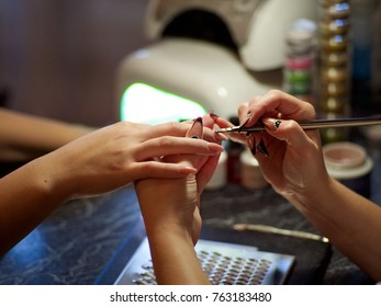 Closeup shot of a woman in a nail salon receiving a manicure by a beautician with nail file woman