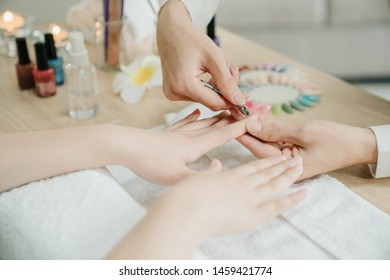 Closeup shot of woman nail specialist using cuticle clipper to give customer manicure in home service. female worker remove cuticle nail with nipper. focus on two asian lady hands at apartment