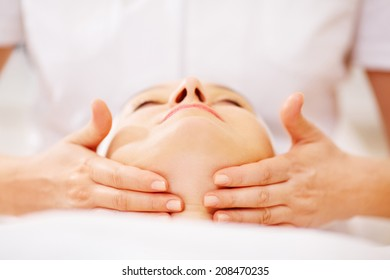 Close-up shot of woman on seance of facial massage with accent on chin