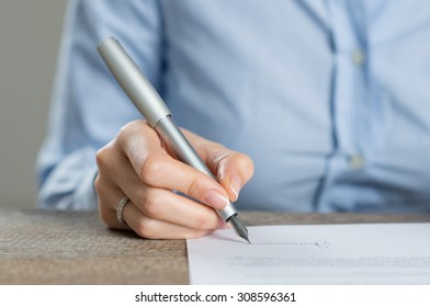 Closeup shot of a woman signing a contract form. Business woman signing a new financial contract. Shallow depth of field with focus on tip of the pen.