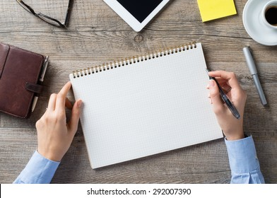 Closeup shot of a woman taking down note in a personal organizer. Business woman is writing in a diary in her office. Blank page to write it on your own message.