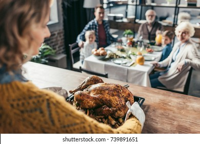 close-up shot of woman with thanksgiving turkey for holiday dinner with family