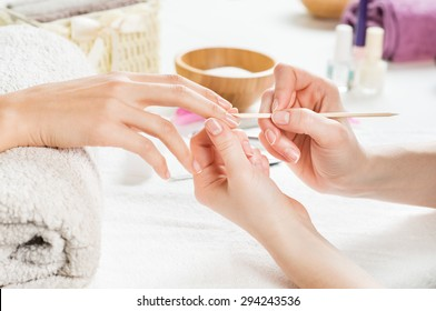 Closeup shot of a woman using a cuticle pusher to give a nail manicure. Nail technician giving customer a manicure at nail salon. Young caucasian woman receiving a french manicure.