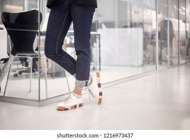 close-up shot of woman wearing jeans and sneakers (smart casual) in white modern office floor, interior. low angle view.