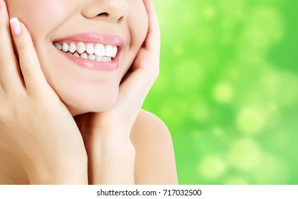 Closeup shot of woman's toothy smile against a green background with copyspace