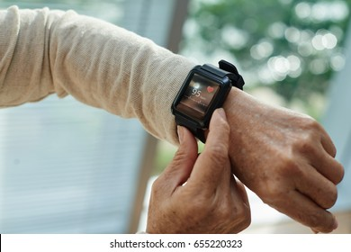 Close-up shot of wrinkled female hand with modern fitness tracker, blurred background