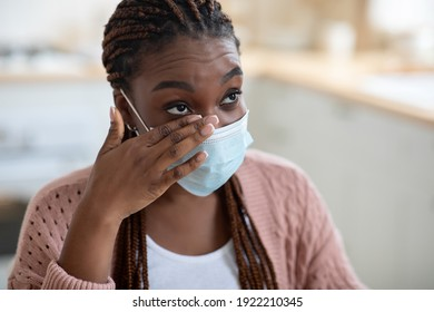 Closeup Shot Of Young African American Woman Wearing Medical Mask Rubbing Her Eye With Dirty Hands, Touching Face, Having Risk Of Coronavirus Spread, Not Following Covid-19 Precautions, Copy Space