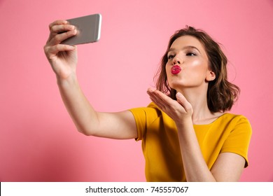 Close-up shot of young attractive woman with bright makeup sending air kiss while taking selfie on mobile phone, isolated over pink background