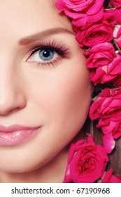 Close-up shot of young beautiful woman face with pink roses in hair