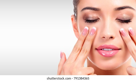 Closeup shot of young beauty woman massaging her face. Facial massage concept. Pretty girl against a grey background with copyspace
