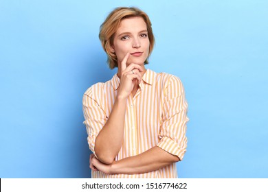 Close-up shot of young blonde woman thinking with finger at a chin.woman having doubtfull expression, close up portrait, facial expression, reaction, curious girl touching her chin with a palm