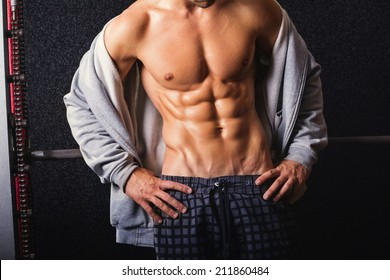 Closeup shot of young bodybuilder with abs. Fit muscular Caucasian man showing his abdominal muscles. Handsome man's torso against dark background.