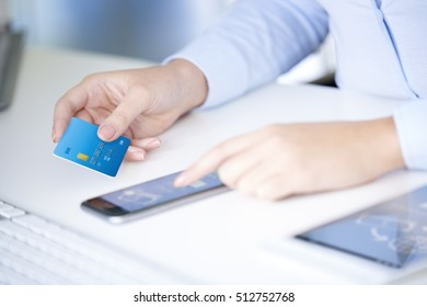 Close-up shot of a young businesswoman holding bank card in her hand while using smartphone app to log in her bank account.