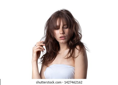 Close-up shot of a young caucasian girl with curly long dark brown hair and bangs. Freckles on the face. White dress. Messy hair. Expressing tenderness. Isolated background