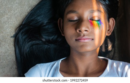 Close-up shot of a young dark skinned girl with sunlight falling on her face with rainbow makeup on closed eyes | proud LGBTQ community, gender fluidity, pride concept