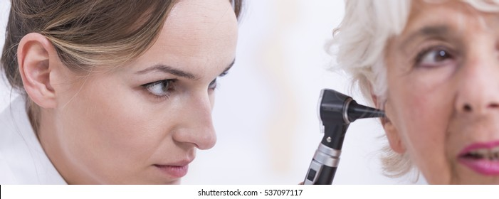 Closeup shot of a young doctor checking her senior patient's ear with otoscope