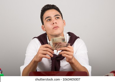 Close-up shot of a young employee sitting at his desk looking up thinking and counting money, holding it in his hand.