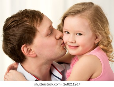 Close-up shot of young father kissing little smiling daughter. Sincere parents love