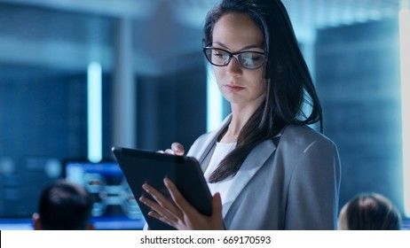 Close-up Shot of Young Female Government Employee Wearing Glasses Uses Tablet in System Control Center. In the Background Her Coworkers are at Their Workspaces with many Displays Showing Valuable Data