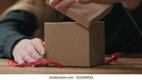 closeup shot of young female hands opens craft paper gift box with red ribbon bow