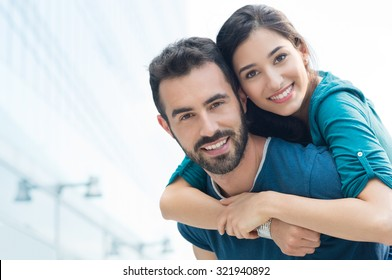 Closeup shot of young man carrying young woman on his back. Happy smiling couple looking at camera. Happy couple putdoor having fun piggyback in love.
