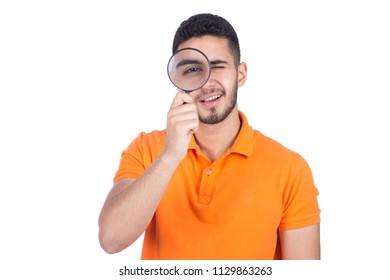 Close-up shot of young man putting the magnifying glass on the eye like a detective, isolated on a white background.