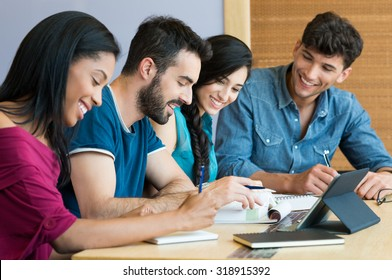 Closeup shot of young man and woman discussing on note. Happy smiling students preparing the exam. Team of students studying together for the university exam.