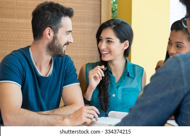 Closeup shot of young man and woman discussing on note. Happy smiling students preparing for the exam. Guy and girl smiling and looking at each other while studying.
