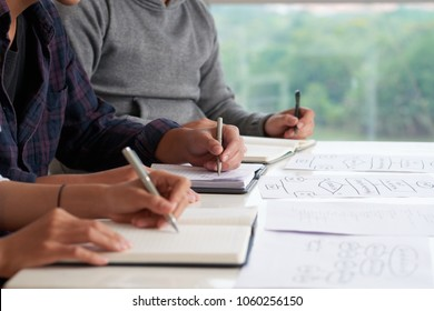 Close-up shot of young managers taking necessary notes while sitting at office desk and participating in working meeting