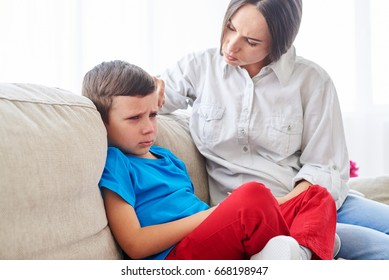 Close-up shot of young mother trying to comfort and calm down her disappointed son
