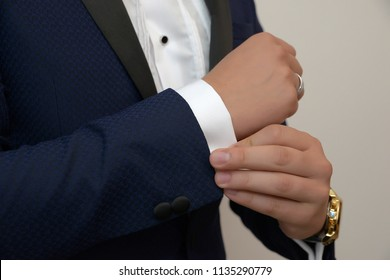 Close-up shot of young white Caucasian male in black tie, fixing his cuff links sign of sprezzatura and elegance. Groom, or sophisticated businessman, or millennial male model getting ready.
