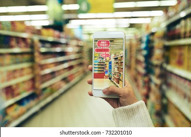 Close-up shot of young woman doing shopping at hypermarket with help of augmented reality app, blurred background