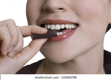 Close-up shot of young woman eating bitter chocolate