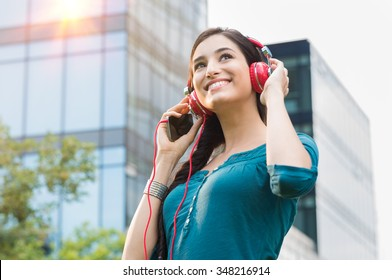 Closeup shot of young woman listening to music with mobile phone in the city center. Happy smiling girl listening to music with professional red headset. Beautiful brunette  young woman feeling free.
